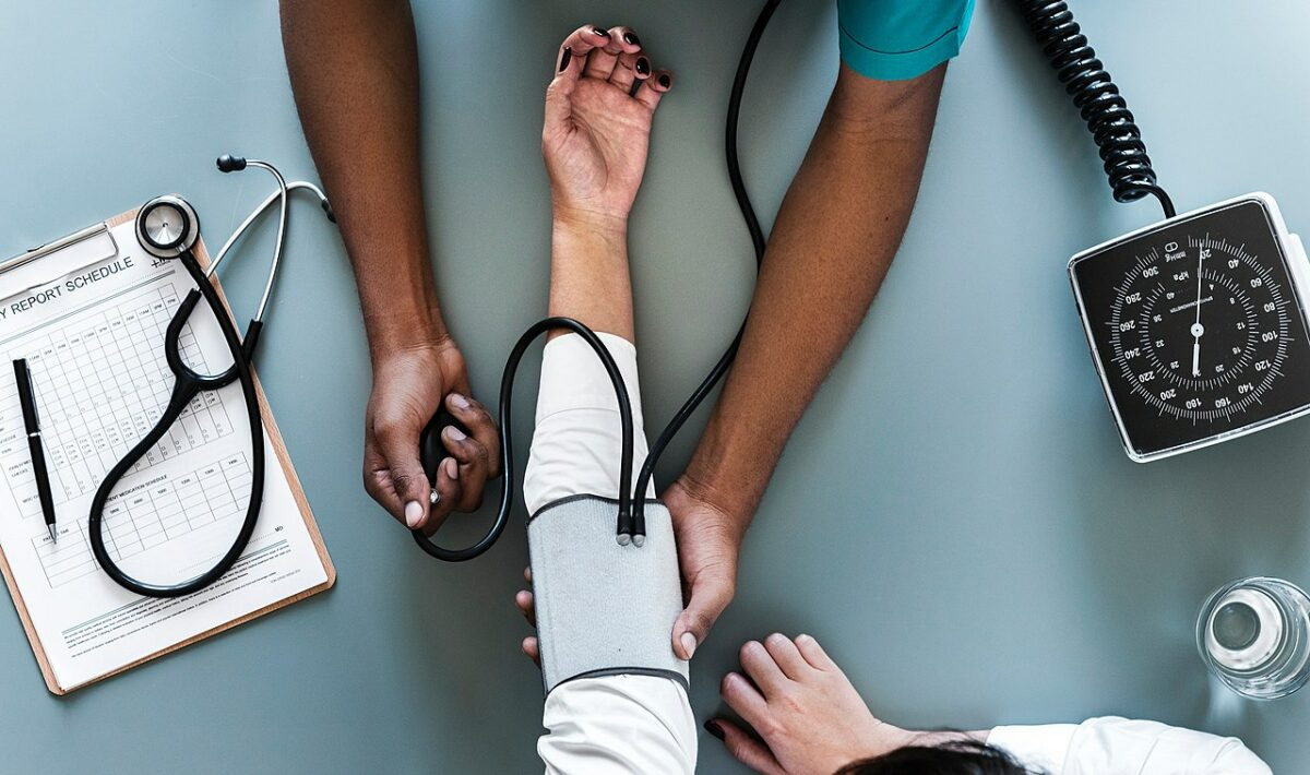 A healthcare professional performing blood pressure monitoring on a patient