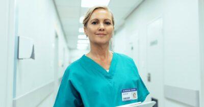 Mature nurse standing in hospital hallway